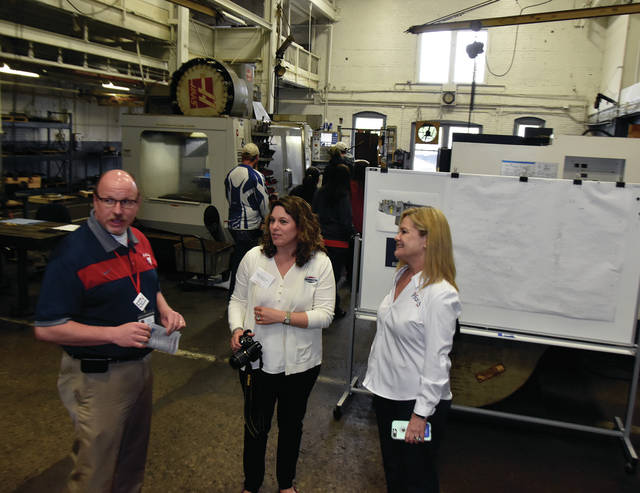 Tayte French-Lutz, center, Director of Marketing for French Oil Mill & Machinery and the fourth generation of the French family to work at the business, gives a tour of the family-owned Piqua manufacturer to Dwayne Thompson, Superintendent of Piqua City Schools and Mayor Kazy Hinds of the City of Piqua, during an open house at the facility last week.