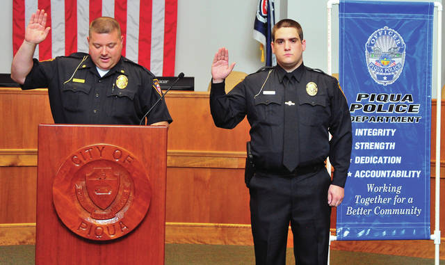 Deputy Piqua Police Chief Jason Preston, left, administers the IACP Law Enforcement Oath of Honor to Piqua's newest officer Kyle Marlett, 27, during ceremonies in the Piqua City Commission Chambers. The Oath, a tradition with Piqua Police, is taken, not only by new officers, but every officer, currently serving and retired, in attendance. The tradition signifies to new officers the support they will receive from fellow officers throughout their law enforcement career. Marlett is a graduate of Kettering Fairmont High School. He graduated from Sinclair Criminal Justice Academy before going to work for the Kettering Health Network where he began as a dispatcher and was later promoted to Police Officer. ©2019 Miami Valley Today, All rights reserved