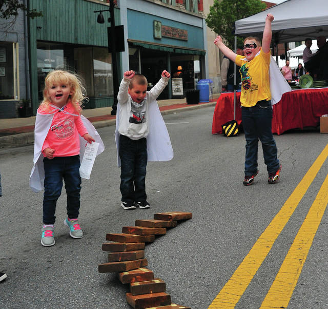 Callie Luthman, 2, William Luthman, 5, and Bryce Thompson, 6, of Piqua cheer as their giant domino blocks fall during Friday's Mainstreet Piqua Downtown Taste of the Arts event.