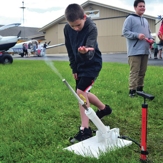 A stream of compressed air streams from the tube as Troy sixth grade student Charles Brower launches his homemade rocket during a Future Begins Today field trip to WACO Field and Aviation Learning Center on Monday. ©2019 Miami Valley Today, All rights reserved