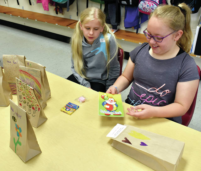 Cookson fifth-graders Alexa Deaton and Kirya Wise display some of the more than 140 gift bags packed by their class to distribute to children at Upper Valley Medical Center.