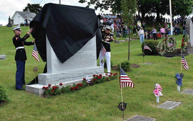 Members of the United States Marine Corps unveil the World War I Memorial at Highland Cemetery in Covington on Monday.
