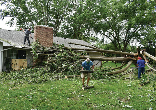 Homeowner Rod Noll pitches in to help workers from Trojan Tree Service in cutting up a large tree that fell on Noll's home at 625 Lincolnshire Drive during Monday's storms. A number of homes in the Merrimont subdivision were affected by the storm. ©2019 Miami Valley Today, All rights reserved