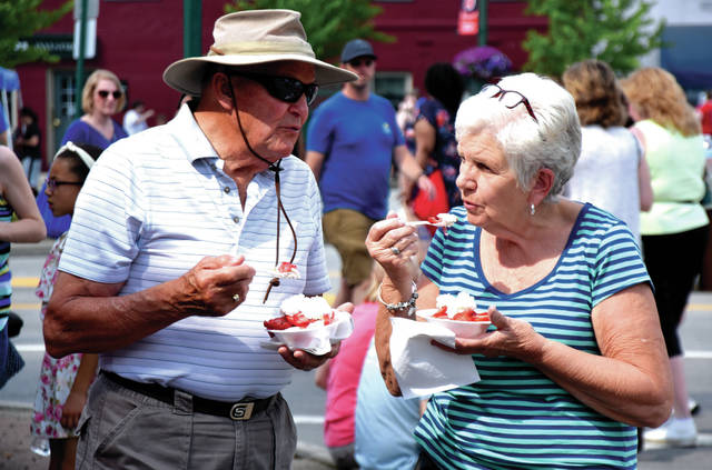 Miami Valley Today file photo Lloyd Schroer of New Bremen and Sharon Leffel of New Knoxville enjoy customized confections during last year's Troy Strawberry Festival.
