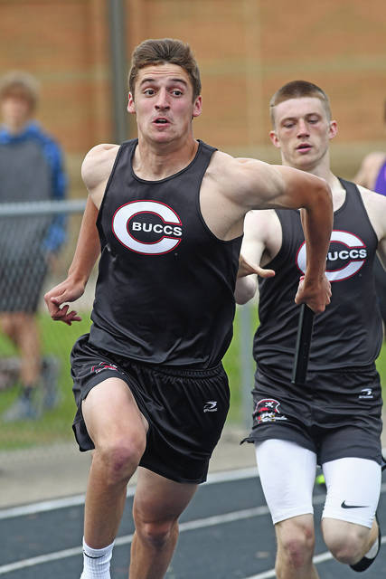 Ben Robinson|GoBuccs.com Covington's Gray Harshbarger takes a handoff from Alex Shaffer in the 800-meter relay Wednesday.