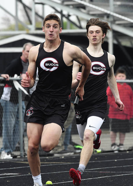 Ben Robinson|GoBuccs.com Covington's Gray Harshbarger takes a handoff from Alex Shaffer in the 800-meter relay Friday at the Covington Invitational.
