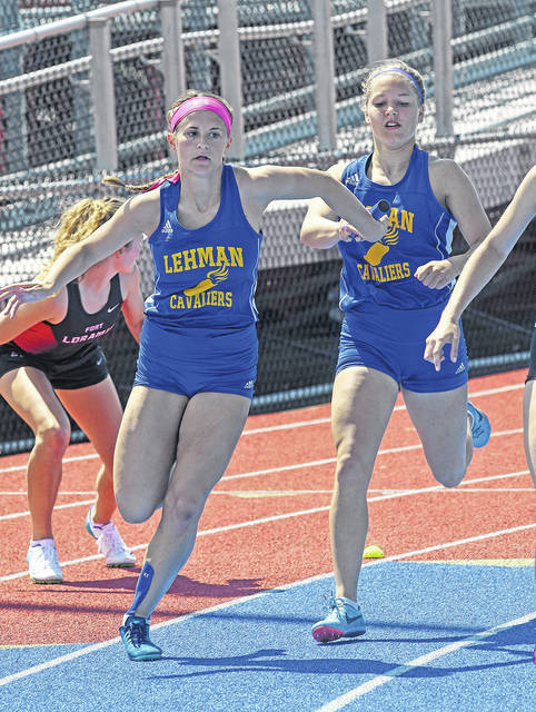 Ben Robinson|GoBuccs.com Lehman Catholic's Lindsey Magoteaux takes a handoff from Olivia Monnin in the 800-meter relay Saturday at Alexander Stadium|Purk Field.