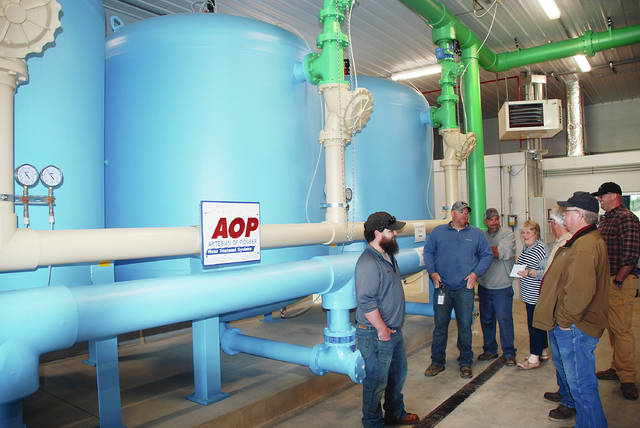 St. Paris Mayor Brenda Cook (center) unveils the new water treatment system on Saturday during a ribbon-cutting and open house. Pictured with Cook are Spencer Mitchell, Greg Kimball, Ben Shuman, Cameron Britenstine, Joe Sampson and Seth Duvendack (of Artisian of Pioneer Water Treatment Systems).
