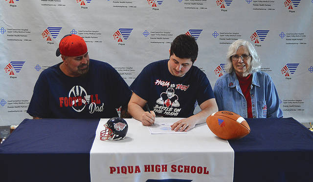Rob Kiser|Call Photo Piqua High School senior Zayne Arbogast signs his letter on intent to play for Bluffton University as his father Frank Arrbogast (left) and grandmother Jackie Trissel (right) look on.