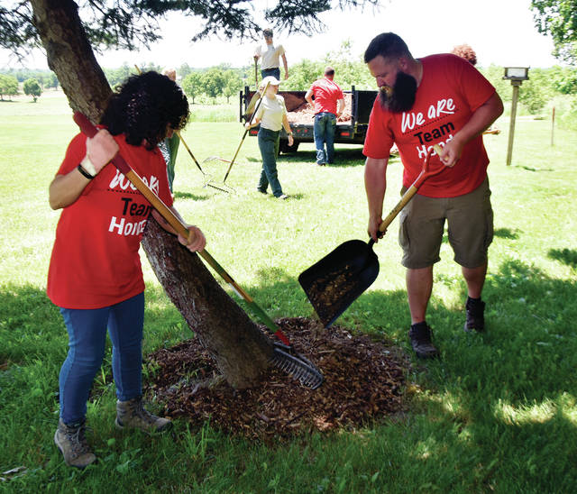 Marcela Magnani, left, and Zach Zabeo of Honda mulch trees around the Miami County Park District's Lostcreek Reserve on Tuesday as part of American Honda Motor Company's week of service to give back to the community. About a dozen Honda employees joined Miami Co. Park District employees to spread more than 30 cubic yards of mulch and wood chips around the park. Tuesday also marked the 60th anniversary of Honda of America's first factory in the United States, a motorcycle plant in Torrence, CA. ©2019 Miami Valley Today. All rights reserved