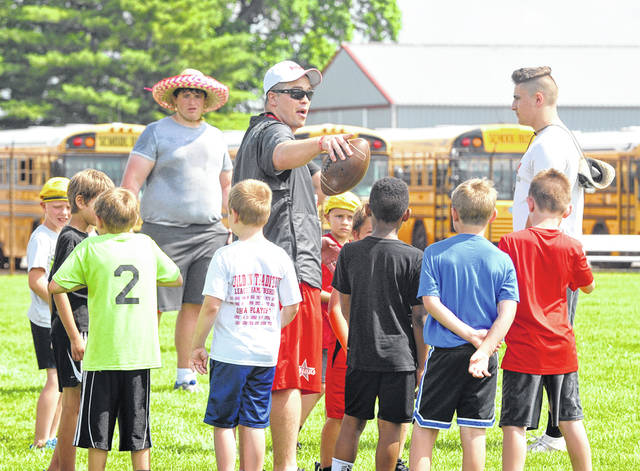 Josh Brown|Miami Valley Today Troy football coach Dan Gress addresses a group of campers as Trojan players Jakob Moorman (back) and Sean Keenan (right) look on during the final day of the Trojans' Little Man's Camp Wednesday at Troy High School.