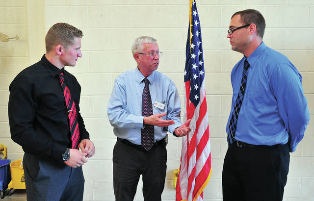 Troy Mayor Mike Beamish, center, talks with Troy's first pair of Fire Apprentices, Joseph Schmeizer, a graduate of Covington High School, and William Vernon, of Piqua, a Lehman High School graduate during a meeting a Troy Fire Department, Station 2, on Monday