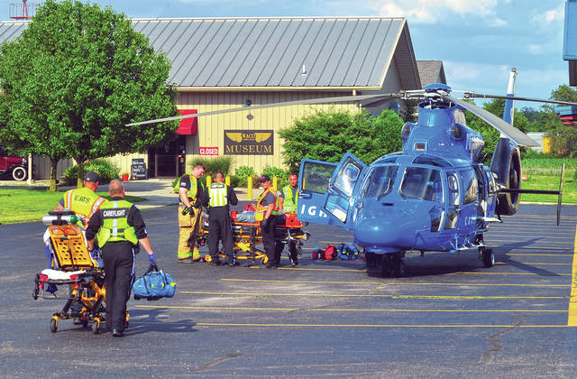 Troy Fire Department medics and CareFlight nurses load a pair of patients aboard the waiting medical helicopter at WACO Field on Wednesday. A head-on crash left two patients requiring transport for care to Miami Valley Hospital.