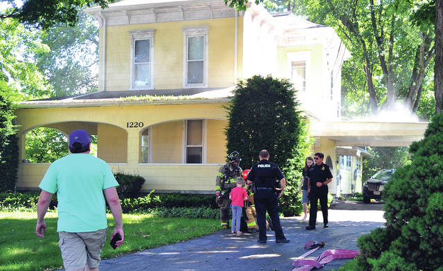 Troy police and firefighters talk to people who were apparently inside this residence at 1220 West Main Street in Troy on Friday afternoon when a fire started. ©2019 Miami Valley Today. All rights reserved