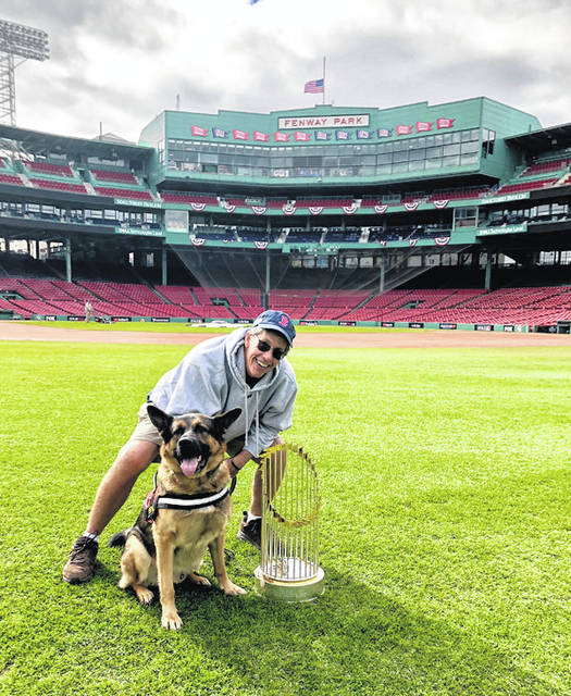 "Provided photo David Mellor, a 1981 Piqua High School graduate, recently released a book, ""One Base at a Time,"" a memoir that shares his struggles with PTSD and his storied career as a groundskeeper for the major leagues, now the senior director of grounds for the Boston Red Sox. Mellor his pictured here with his service dog Drago, a regular at Fenway Park, and the team's World Series trophy from 2018."