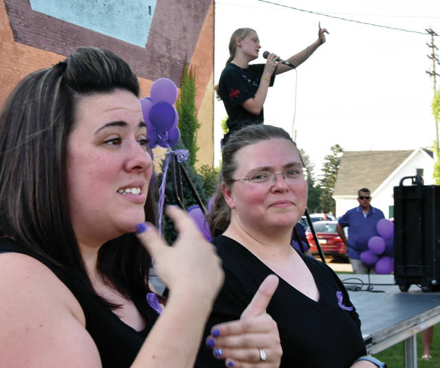 Aimee Applegate, far left, of West Milton, signs a memorial on Prouty Plaza in downtown Troy on Friday evening, honoring Troy High School American Sign Language teacher Karen Husa who recently passed away from cancer. The celebration included sharing memories of the popular teacher, songs, a candle-lighting ceremony and a balloon release. ©2019 Miami Valley Today. All rights reserved
