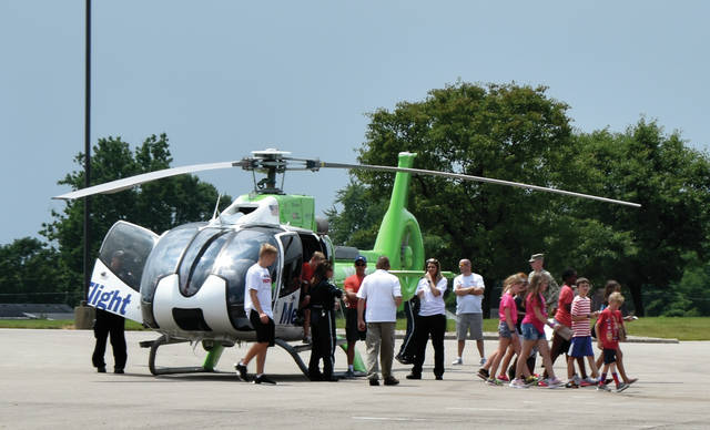 Participants in the Miami County Sheriff's Office's Youth Camp explore a Kettering Health Network MedFlight helicopter as part of their camp activities on Wednesday.