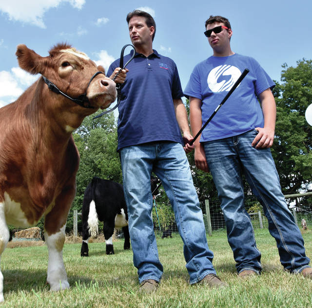 Adam Sharp, executive vice president of the Ohio Farm Bureau Federation, left, gets showmanship tips from Sam Sutherly, 15, of Elizabeth Township, last week as he works Sutherly's steer, Buttercup<em>,</em> in preparation for the upcoming Dean's Charity Steer Show in Columbus.