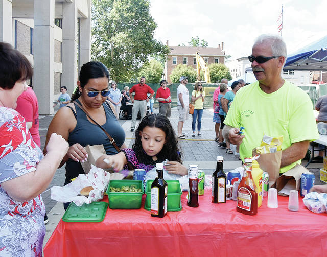 Kim Block, Marcela Wigley, and her daughter Faith Block, 7, l-r, and Concord Twp. employee Neil Rhoades check out the condiments table during Friday's Miami Co. Cattleman's Association Lunch on the Lawn event in Troy. The monthly luncheon is held on the last Friday of the month throughout the summer from 11 a.m. to 1 p.m. The event averages 275-300 ribeye steaks per month, along with 150-175 hamburgers and 50-100 hotdogs. ©2019 Miami Valley Today. All rights reserved