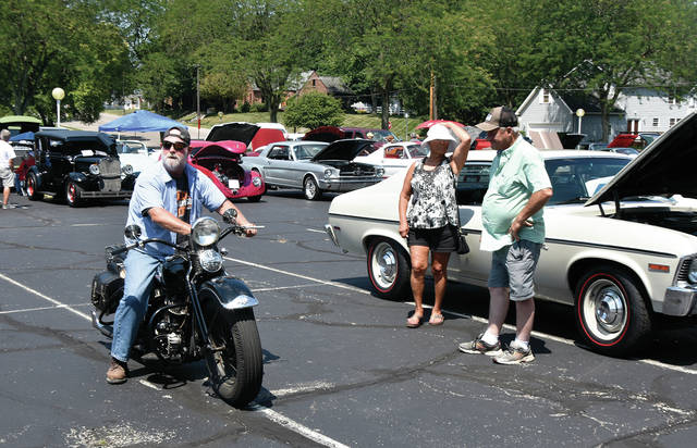 Admirers gather as Jerry Lewis of Tipp City arrives at the ITW/Hobart Car Show on his Harley Davidson, a 1947 frame with a 1941 engine and tank, on Saturday. The event, which featured more than 100 vehicles, benefits the American Cancer Society.