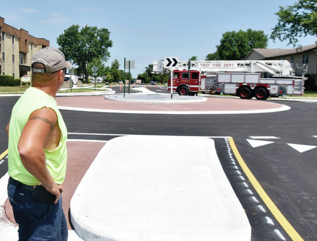 A City of Troy employee watches Troy Fire Department Tower 1 negotiated the new roundabout at McKaig and Dorset on Tuesday. Several large vehicles were brought out to make sure that drivers of large vehicles arre comfortable with the new traffic pattern. The city is expected to set an opening date soon. ©2019 Miami Valley Today. All rights reserved