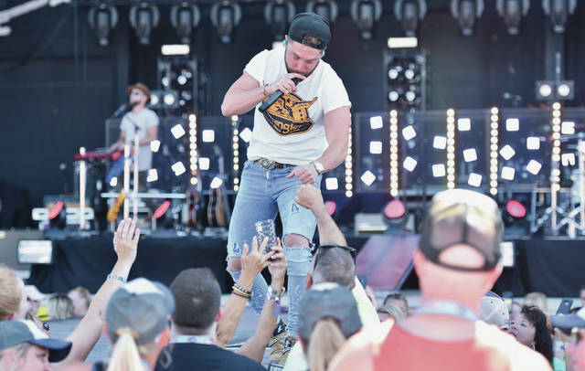 Chris Lane greets his fans with fist bumps and hand shakes as the first performer to take the main stage at Country Concert on Friday, July 12.