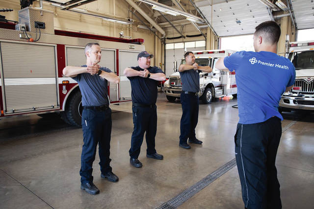 Provided photo Troy firefighter/paramedics work with Mitchell Simmons, at right, of Premier Health's Healthy Heroes fitness and wellness program.