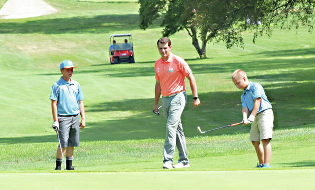 Rob Kiser|Miami Valley Today Piqua Country Club assistant pro Braden Hengst looks on as Miami Shores' Ben Maxson prepares to chip on to the first green at Piqua Country Club and teammate Ty Schauer looks on.