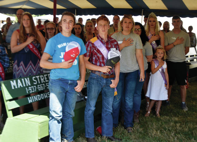 Miami County Fair royalty and Jr. Fair Board members recite the Pledge of Allegiance during opening ceremonies for the 2019 Miami County Fair on Friday.