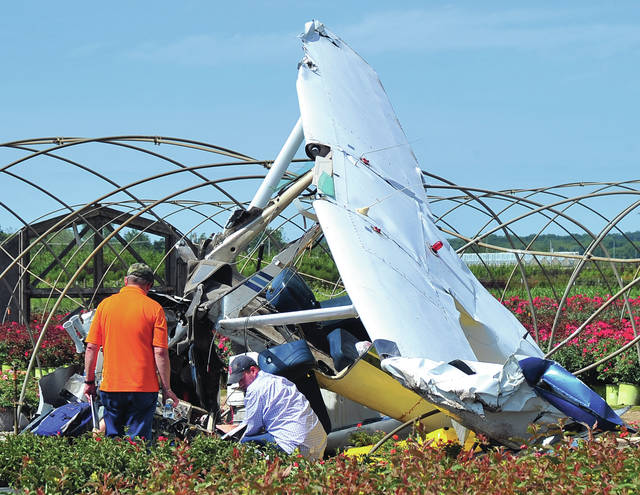 Investigators work at the scene of an airplane crash near the Andy Barnhart Airport in New Carlisle on Sunday morning.