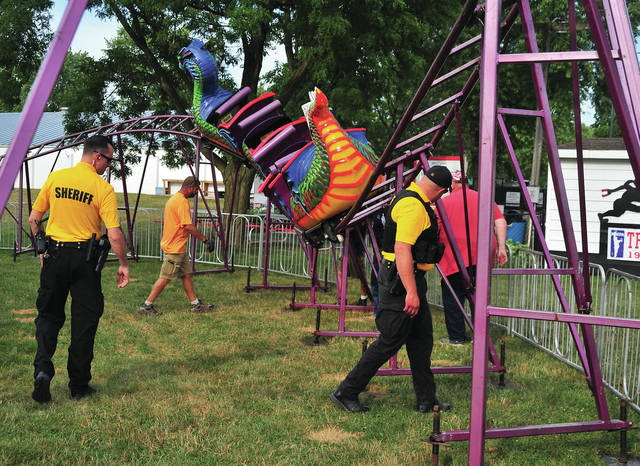 Miami County Sheriff's Deputies, Miami Co. Fair officials, and amusement ride representatives, look over the Dragon Wagon ride at the Miami County Fair on Sunday after it apparently malfunctioned twice within a twenty-four hour period.