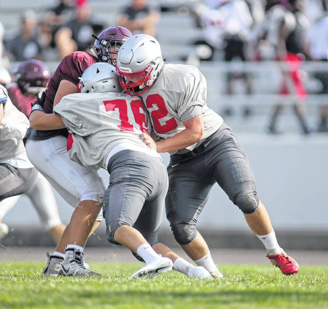 Lee Woolery|Miami Valley Today Troy's Sean Keenan (76) and Adam DeCerbo (52) stuff a Lebanon ballcarrier during a scrimmage Friday night at Troy Memorial Stadium.