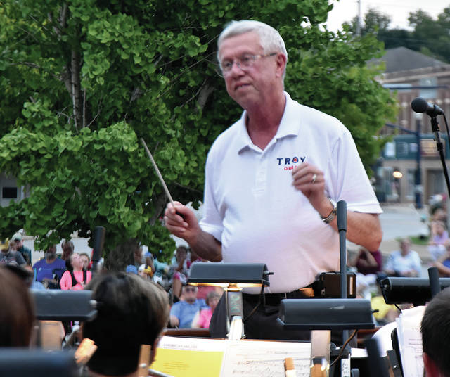 """Troy Mayor Mike Beamish conducts the Dayton Philharmonic Orchestra in """"His Honor March,"""" during the annual Mayor's Concert on Prouty Plaza on Sunday. The concert was Beamish's 16th and final concert as Mayor of Troy."""