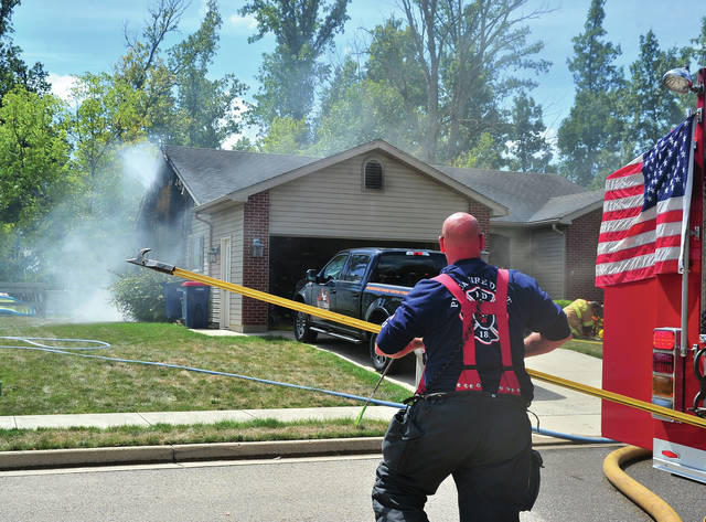 Piqua Firefighter Aaron Kuhn brings a pike pole to assist at a structure fire on Laura Drive on Sunday afternoon.