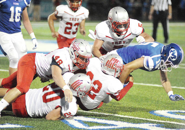 Anthony Weber|Miami Valley Today file Troy's Zack Schwausch (48) brings down a Miamisburg runner with a host of teammates during a game in 2017.