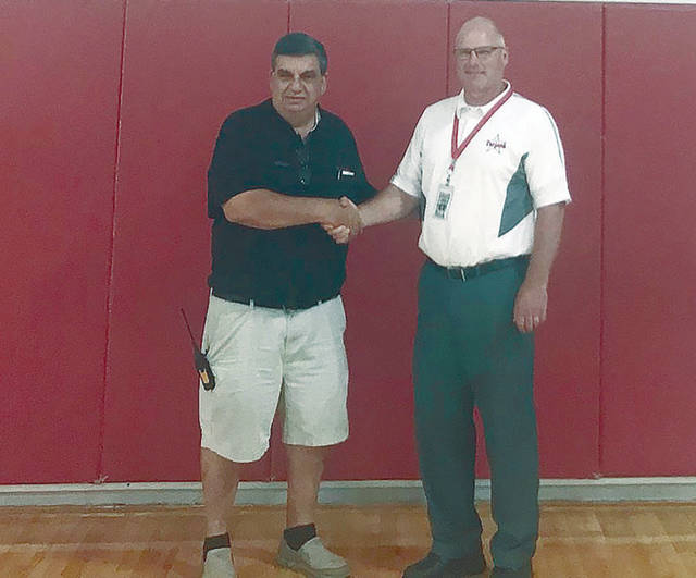 Provided photo True Value Western Ohio Hardware general manager Bruce Fisher shakes hands with Troy City Schools Director of Transportation, Facilities and Maintenance Tytus Jacobs recently at Troy Junior High School after presenting Jacobs with 30 gallons of paint and sundries, provided by the True Value Foundation Painting a Brighter Future grant.