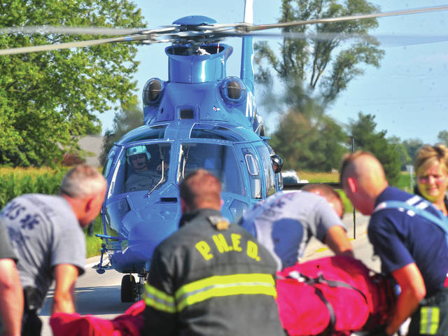Firefighters from Pleasant Hill and Covington assist CareFlight nurses in loading a victim of a head-on crash to a waiting helicopter on State Route 41 on Monday afternoon between Troy and Covington.
