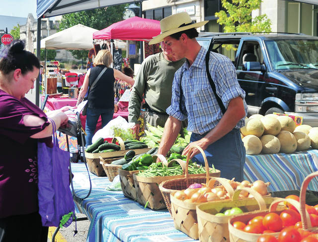 Joel Burns of Burns' Market in Covington assists a customer at the Piqua Farmers Market on Thursday. Next week will be the final Piqua Farmers Market of the 2019 season.