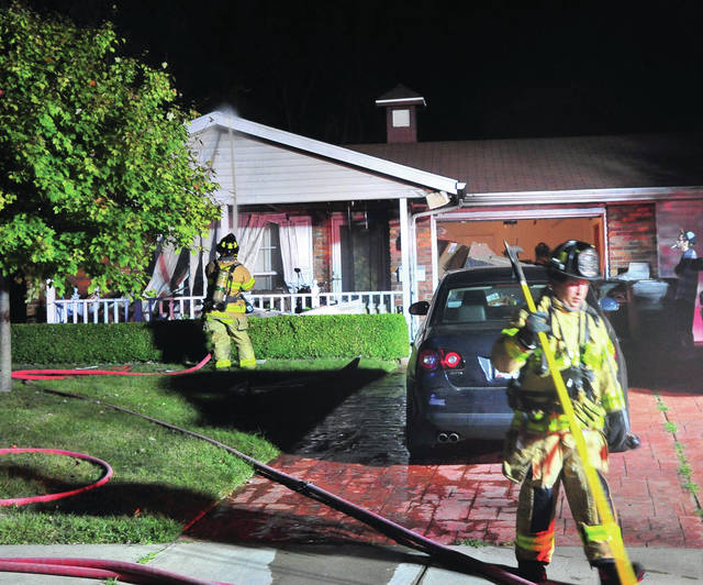 Troy firefighters extinguish a fire that began on a porch at a Heather Road duplex on Saturday evening.