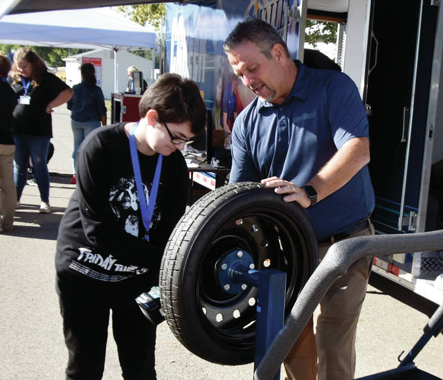 Lydia Yount, a student at Troy Junior High School, learns how to change a tire from Tony Trapp of the Upper Valley Career Center during the Made in Miami County event at the Miami County Fairgrounds. The event, put on by the Troy Area Chamber of Commerce, was attended by more than 700 students from around Miami County.