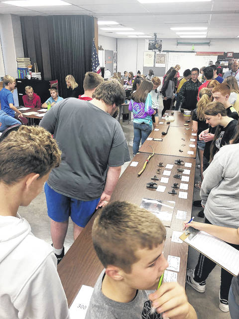 Provided photo Troy Junior High School eighth graders examine objects found during their annual archaeological dig program.