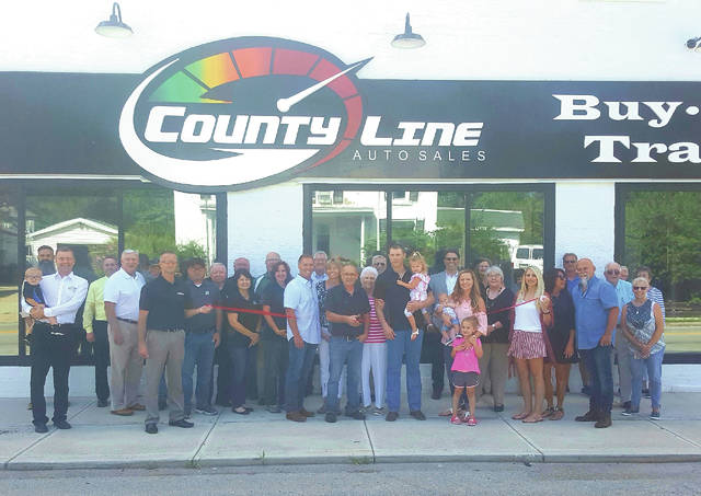 Provided photo Pictured are the proud owners of County Line Auto Sales, Kevin Welch and Dustin Kimmel, other members of the Kimmel family, and members of the Covington Chamber of Commerce during a ribbon-cutting ceremony for the business on Aug. 23.