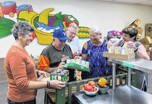 "From left to right, First Place Food Pantry board of directors member Ann Welch; volunteers Mike Risheill and Larry Kinder; FPFP Executive Director Donna Wilkerson; and board member Sharon Buse work to unbox food at the pantry, located at 721 Lincoln Ave., in Troy. Two of the pottery bowls donated for the ""Bowls of Hope"" event are pictured in front."