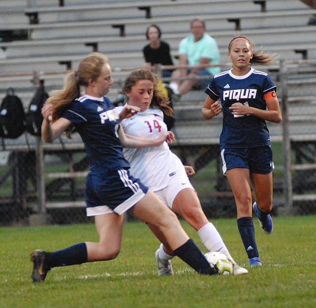 Rob Kiser|Miami Valley Today Tippecanoe's Hannah Rittenouse is stopped by Piqua's Rachel Cavender as Whitney Evans closes in.