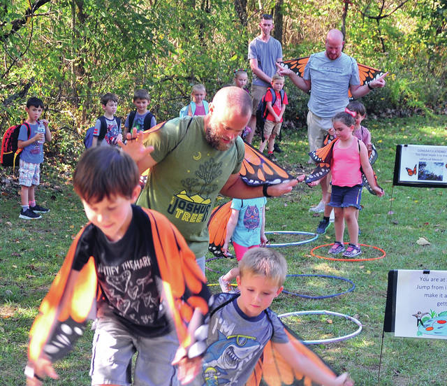 Miami East Elementary kindergarten teachers Preston Elifritz, front, and Justin Roeth, back right, lead their classes through a butterfly obstacle course during a field trip to the Miami County Park District's Stillwater Prairie on Tuesday. ©2019 Miami Valley Today. All rights reserved