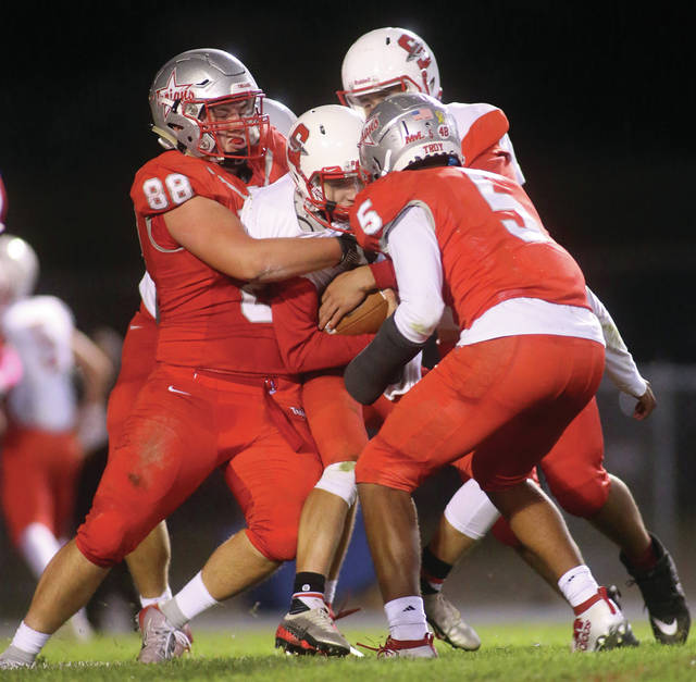 Lee Woolery|Miami Valley Today Troy's Adam DeCerbo (88) and J.J. McCoy (5) stop a Stebbins ballcarrier Friday at Troy Memorial Stadium.