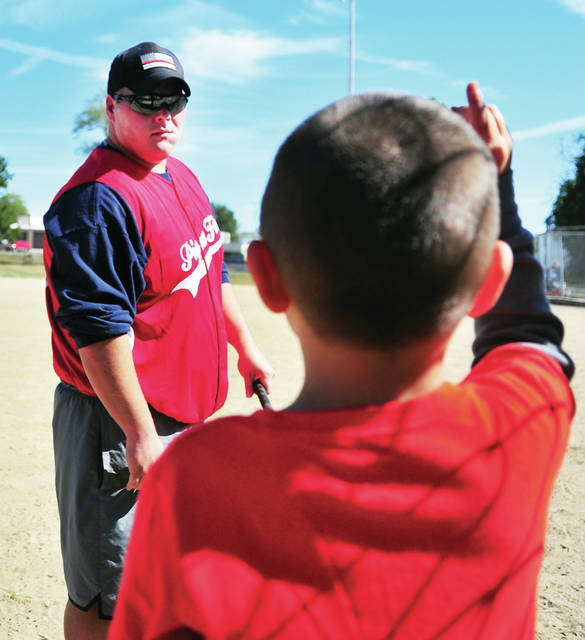 Piqua firefighter Jordan Vail, left, gets some last-minute hitting instruction from his son Greyson before stepping to the plate during Saturday's Battle of the Badges charity softball tournament at Mote Park. Proceeds from the tournament will go to Riverside of Miami County along with Miami, Darke, and Shelby County Boards of Development Disabilities. The event was organized and sponsored by Thrivent Financial Services. ©2019 Miami Valley Today. All rights reserved.