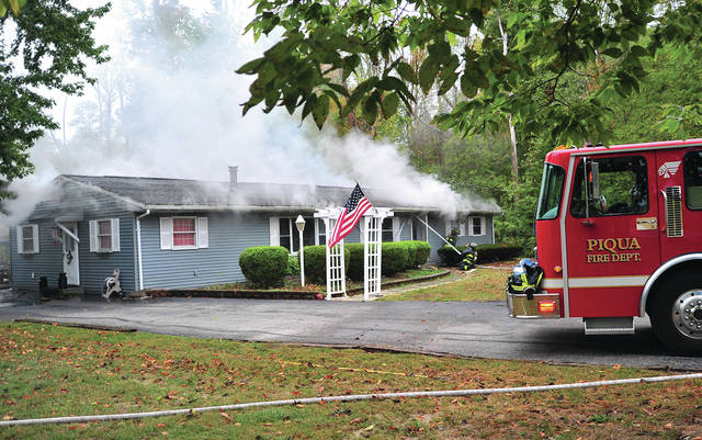 Firefighters battle a house fire in the 200 block of Snodgrass Road, north of Piqua, on Monday morning.