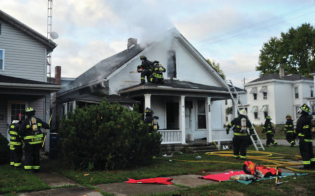 Firefighters from Piqua and Covington battle a house fire at the corner of Greene and College Streets in Piqua on Wednesday morning.