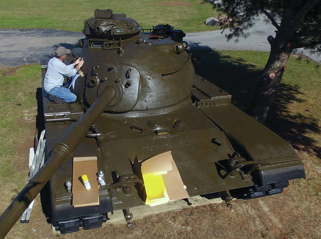 Mike Haines of Piqua applies some of the finishing touches to a M-60 tank that sands in front of the Troy VFW Post on LeFevre Road. The tank had been sitting on the property since around 1989 and after seeing the tank's deteriorating condition, Haines, a U.S. Army veterans, took it upon himself to do some exterior restoration work on the vehicle.